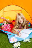 Children girl writing notebook in camping tent with flowers — Stock Photo