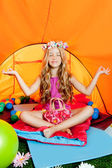Blond little girl practicing yoga in orange camping tent — Stock Photo