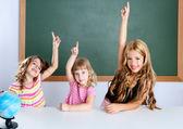 Kids student clever girls in classroom raising hand — Stockfoto