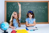 Clever nerd student girl in classroom raising hand — Stock Photo