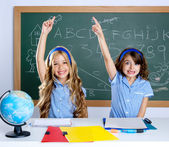 Clever students in classroom raising hand — Stock Photo