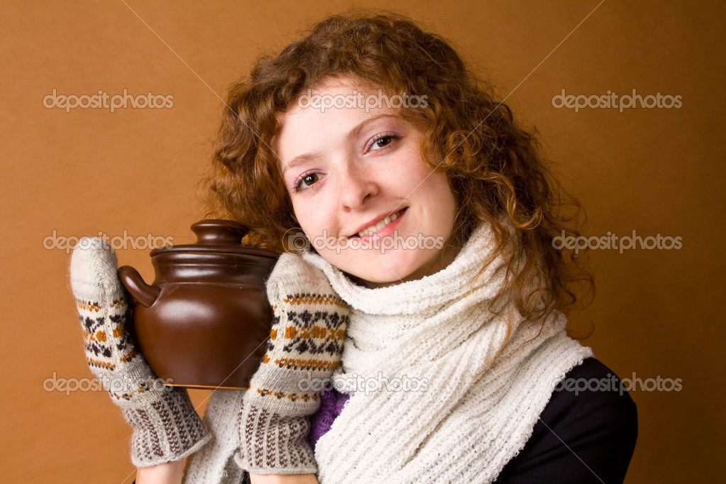 The beautiful girl with in mittens and with a pot on a sand background — Stock Photo #6612724