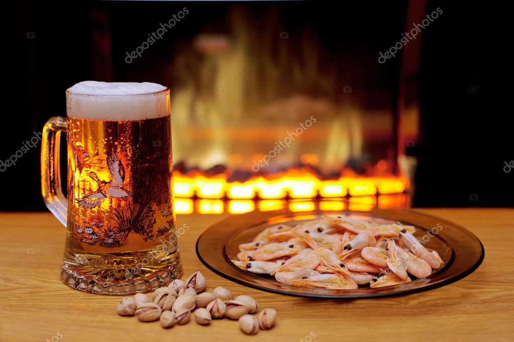 Glass of beer, plate with shrimps, the pistachios, located on a table, situated opposite to the flame of a fireplace. — Stock Photo #6151340