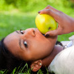 Beautiful black woman eating an apple — Stock Photo