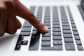 Black finger typing on computer keyboard — Stock Photo