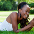 Royalty-Free Stock Photo: Teenage black girl using a phone, lying on the grass