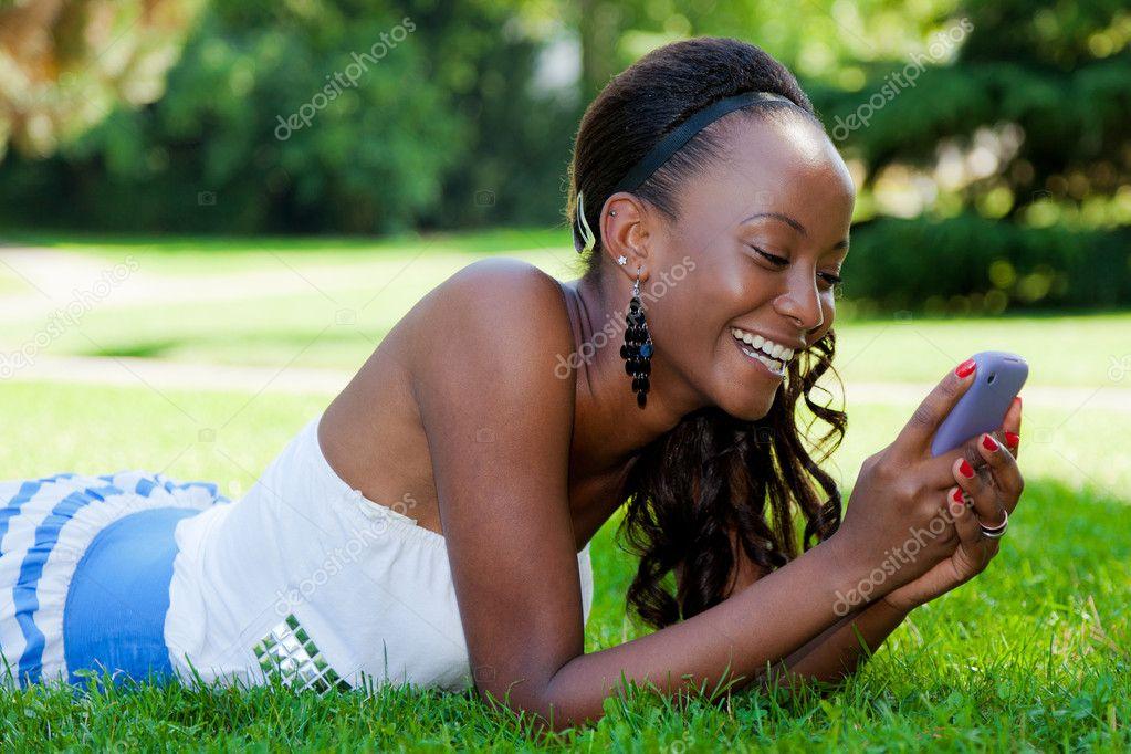 Smiling Teenage Black Girl Using A Phone, Lying On The