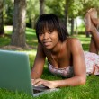Royalty-Free Stock Photo: Outdoor portrait of young black woman using a laptop