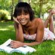 Outdoor portrait of young black woman reading a book — 图库照片