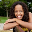 Beautiful african american woman sitting on a bench — Photo