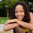Beautiful african american woman sitting on a bench — Stock Photo