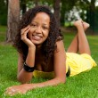 Young black woman lying down on the grass — Stock Photo #6634126