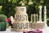 Luxurious wedding cake and two champagne flute glasses — Stock Photo