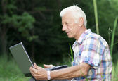 An elderly man with a laptop — Stock Photo