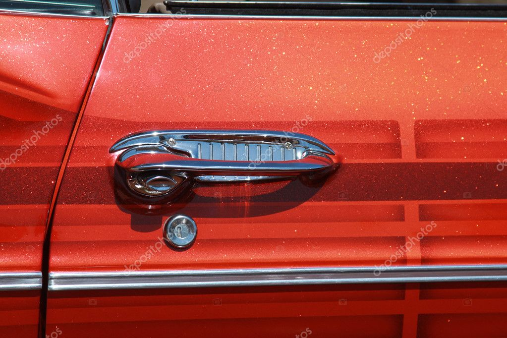 A shiny chrome car door handle and lock of a classic car  Stock Photo #5590277