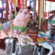 Pigs and horses on carousel - Stok fotoğraf