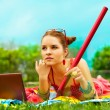 Stock Photo: Beautiful young womwith laptop and pencil on green grass