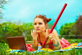 Beautiful young woman with laptop and pencil on green grass — Stock Photo
