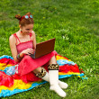 Beautiful young woman with laptop on green grass — Stock Photo