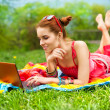 Stock Photo: Beautiful young womwith laptop on green grass