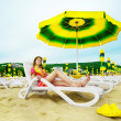 Beautiful woman laying on the beach under umbrella — Stock Photo