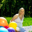 Royalty-Free Stock Photo: Pregnant woman sitting in colorful baloons