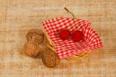 The basket with dark red cherry and nuts — Stock Photo