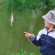 Young boy and small fish — Stock Photo