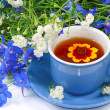 Blue cup of tewith flowers — Stock Photo #5991317