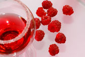 The glass of transparent liquor and raspberry — Stock Photo