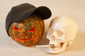 The cheerful halloween pumpkin and skull with cigarette — Stock Photo