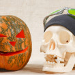 The big cheerful halloween pumpkin and skull with sigarette — Stock Photo