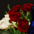Bouquet red and creamy roses and blue bottle neck — Stock Photo #6105253