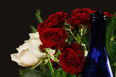 The bouquet red and creamy roses and blue bottle neck — Stock Photo