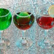 The three glasses of green and red liquor and lemon — Stock Photo