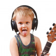 图库照片: Little boy with headphones and guitar