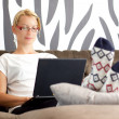 Beautiful young lady sitting on sofa, using laptop — Stock Photo