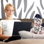 Beautiful young lady sitting on sofa, using laptop — Stock Photo