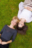 Two girls lying in the grass — Stock Photo