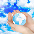 Hands holding earth in the sky — Stock Photo