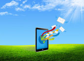 Tablet pc sending email on the green field — Stock Photo
