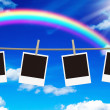 Blank photo frames hanging against rainbow sky - Stock Photo