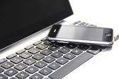 Smart phone on laptop keyboard — Stock Photo