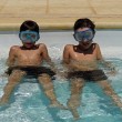 Boys with goggles in swimming pool — Stock Photo