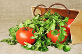 Tomatoes and parsley in a paper package — Stock Photo