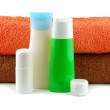 Cosmetic bottles with bath towels — Stock Photo