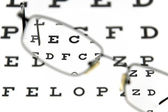 Eyeglasses and eye test chart — Stock Photo