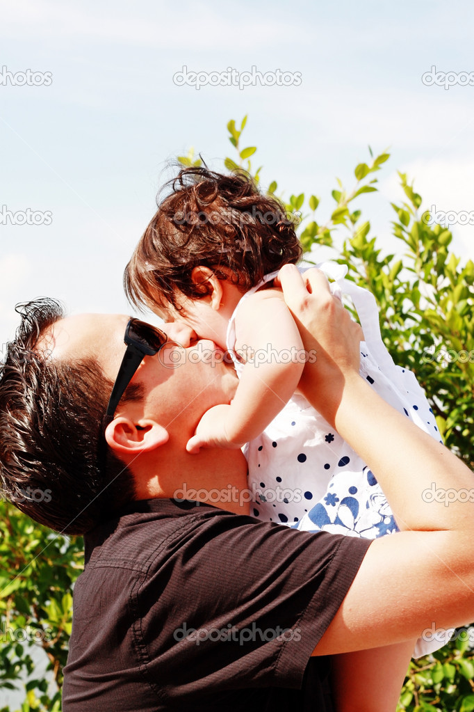 Father in early thirties gives his daugther a kiss on the cheek in the park   Stock Photo #5692239