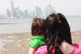 母彼女の赤ちゃん何か面白いもので示します海 — ストック写真