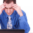 Male frustrated with work sitting in front of a laptop. - Stock Photo